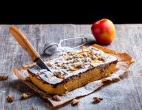 Äppelpaj som dammas av med det pudrade socker och snittet med en kniv Rött Arkivfoton