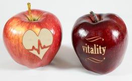 1 äpple med inskriftvitaliteten och ett äpple med en hjärta Fotografering för Bildbyråer