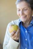 äpple som äter den gammalare kvinnan Arkivbild