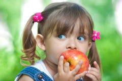 äpple som äter flickan little utomhus- röd sommartid Arkivbild