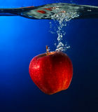 äpple som faller för att water Arkivbilder