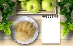 Äpplegrapefrukt och vitanmärkningsbok under lönnlöv Royaltyfri Fotografi