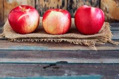 Äpplen av lantgården på trä Arkivbilder