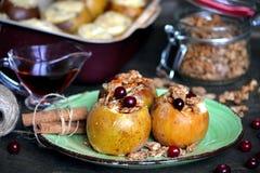 Äpplen bakade med honung, muttrar och granola Arkivfoto