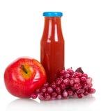 Äpplen, druvor och fruktsaftflaska som isoleras på vit Royaltyfri Foto