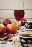 Äpplen, en kopp te och ett exponeringsglas av vin Royaltyfria Foton