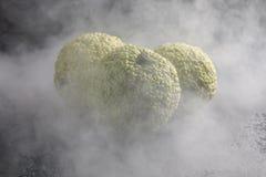 Äpplen för Adam ` s på en svart bakgrund i rök Äpplen för Adam ` s, som drakeägg som slås in i rök Arkivfoton