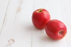 Äpplen för rosa dam på ett målat trä Fotografering för Bildbyråer