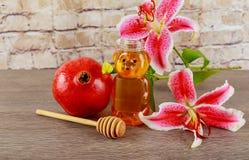 Äpplen, granatäpplen och honung på en tappningmaträtt i köket table trä Den traditionella inställningen för det judiska nya året  Arkivfoto