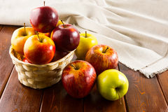Äpplen i den lilla vide- korgen på mörk träbakgrund Royaltyfria Foton