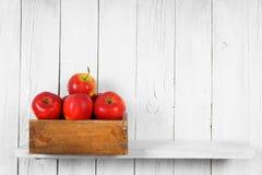 Äpplen i en ask på trähylla Royaltyfri Fotografi