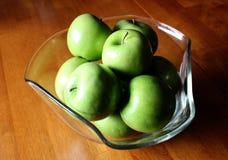 Äpplen i en dekorativ bunke på en Wood tabell Royaltyfria Bilder