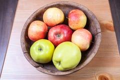 Äpplen i en gammal träbunke Arkivbild
