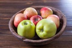 Äpplen i en gammal träbunke Arkivbilder