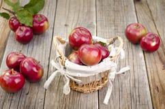 Äpplen i en korg på en trätabell royaltyfria foton