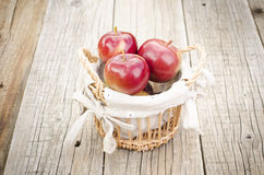Äpplen i en korg på en trätabell Arkivbilder