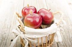 Äpplen i en korg på en trätabell arkivbild