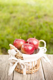 Äpplen i en korg på en trätabell- och gräsplanbakgrund royaltyfria foton