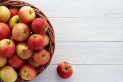 Äpplen i en korg på träbakgrund Arkivfoto