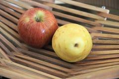 Äpplen i en korg på trätabellen royaltyfri foto