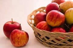 Äpplen i en vide- korg Arkivfoto