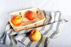 Äpplen i korg och på handduken Arkivbilder