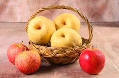 Äpplen i korg på en wood bakgrund Arkivbilder