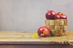 Äpplen i korg på trätabellen Nya gårdsprodukter Arkivbilder