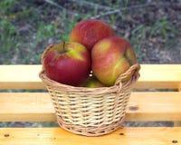 Äpplen i ljus - brun vide- korg på trätabellen Royaltyfria Foton