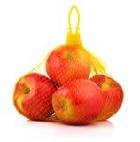 Äpplen i plast- Mesh Sack på vit bakgrund arkivbilder