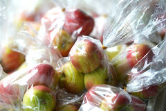 Äpplen i plastpåsar Arkivbild