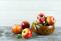 Äpplen i träbunke på den lantliga bakgrunden Fotografering för Bildbyråer