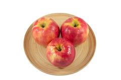 Äpplen i träplatta på en vit bakgrund Arkivbild