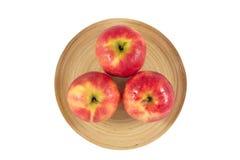 Äpplen i träplatta på en vit bakgrund Royaltyfri Bild