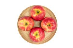 Äpplen i träplatta på en vit bakgrund Royaltyfri Fotografi