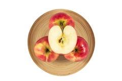 Äpplen i träplatta på en vit bakgrund Royaltyfri Foto