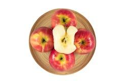 Äpplen i träplatta på en vit bakgrund Royaltyfria Bilder