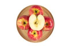 Äpplen i träplatta på en vit bakgrund Arkivfoto