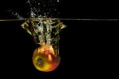 Äpplen i vatten med reflrction och färgstänk Fotografering för Bildbyråer