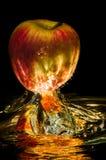 Äpplen i vatten med reflrction och färgstänk Royaltyfri Fotografi
