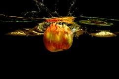 Äpplen i vatten med reflrction och färgstänk Arkivbild