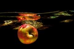 Äpplen i vatten med reflrction och färgstänk Royaltyfria Bilder