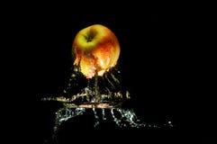 Äpplen i vatten med reflrction och färgstänk Arkivfoton