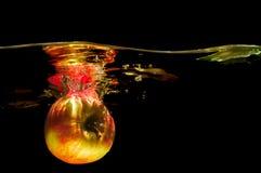 Äpplen i vatten med reflrction och färgstänk Arkivfoto