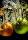 Äpplen i vatten med reflrction och färgstänk Arkivbilder