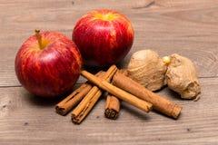 Äpplen, kanelbruna pinnar och ingefära överst av en tabell Royaltyfri Foto