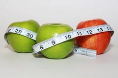 Äpplen med att mäta bandet - hälsa Arkivbild