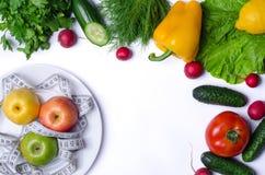 Äpplen med att mäta bandet och nya grönsaker som isoleras på whit Arkivbilder