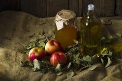 Äpplen med en krus av honung och en flaska av olivolja Arkivfoto