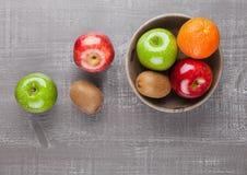 Äpplen med kiwin och apelsinen i träbunke Royaltyfri Bild